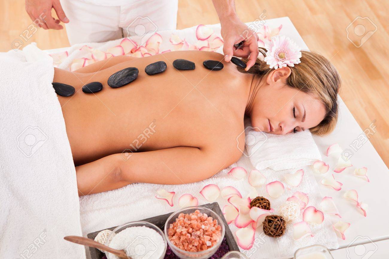 Hot stones lined on her back promotes relaxation. Stock Photo - 16522017