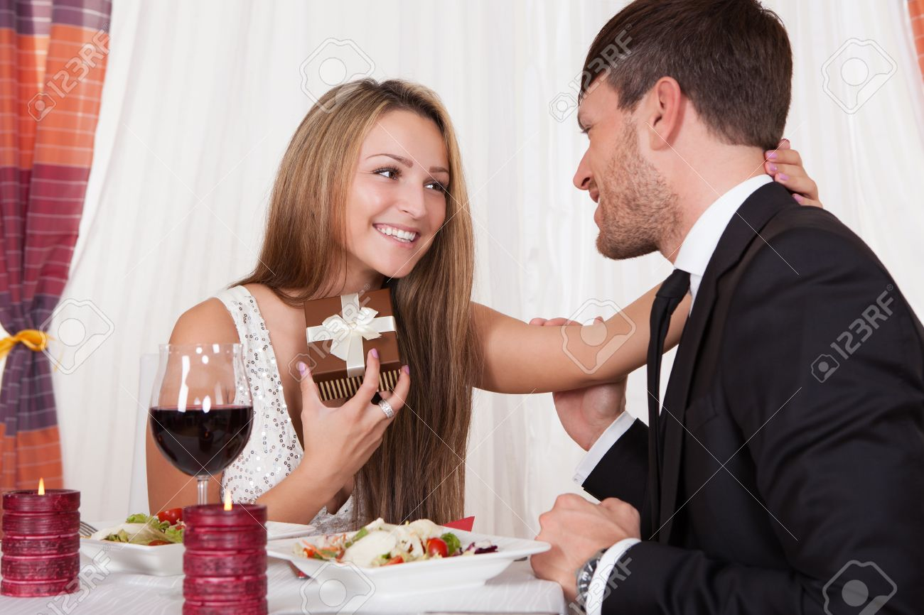 2b72d9e24aae Happy young woman receives a gift from her partner. Romantic dinner setting  with young couple