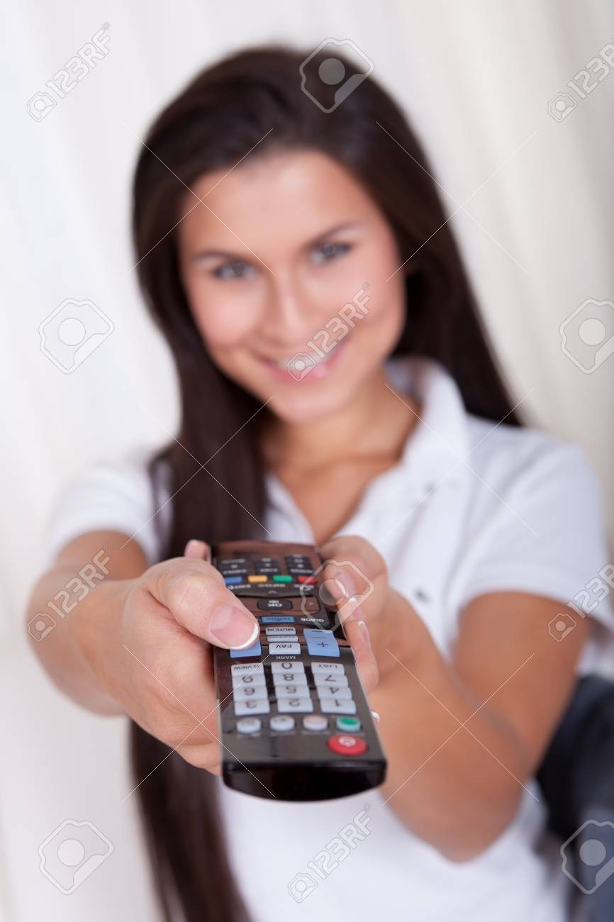 Smiling woman sitting on a couch with a remote control in her hands with copyspace over white curtains Stock Photo - 16522277