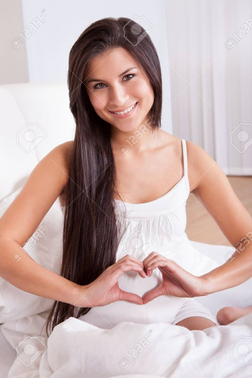 Beautiful smiling pregnant woman sitting on a bed making a heart sign with her fingers over her swollen belly Stock Photo - 16522436