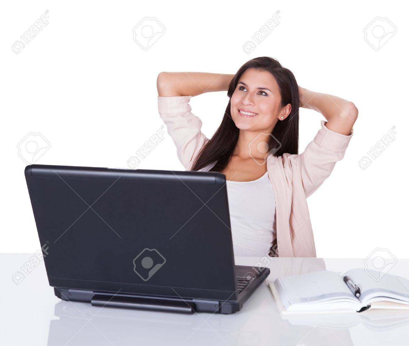 Attractive confident young professional woman sitting working at her laptop with an open book alongside her Stock Photo - 16522604