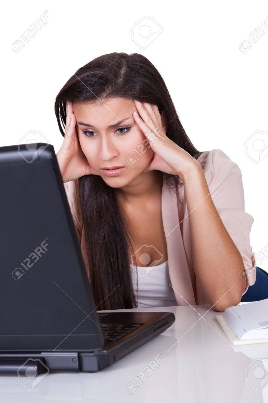Unmotivated young businesswoman seated at her desk staring despondently at her laptop Stock Photo - 16522514