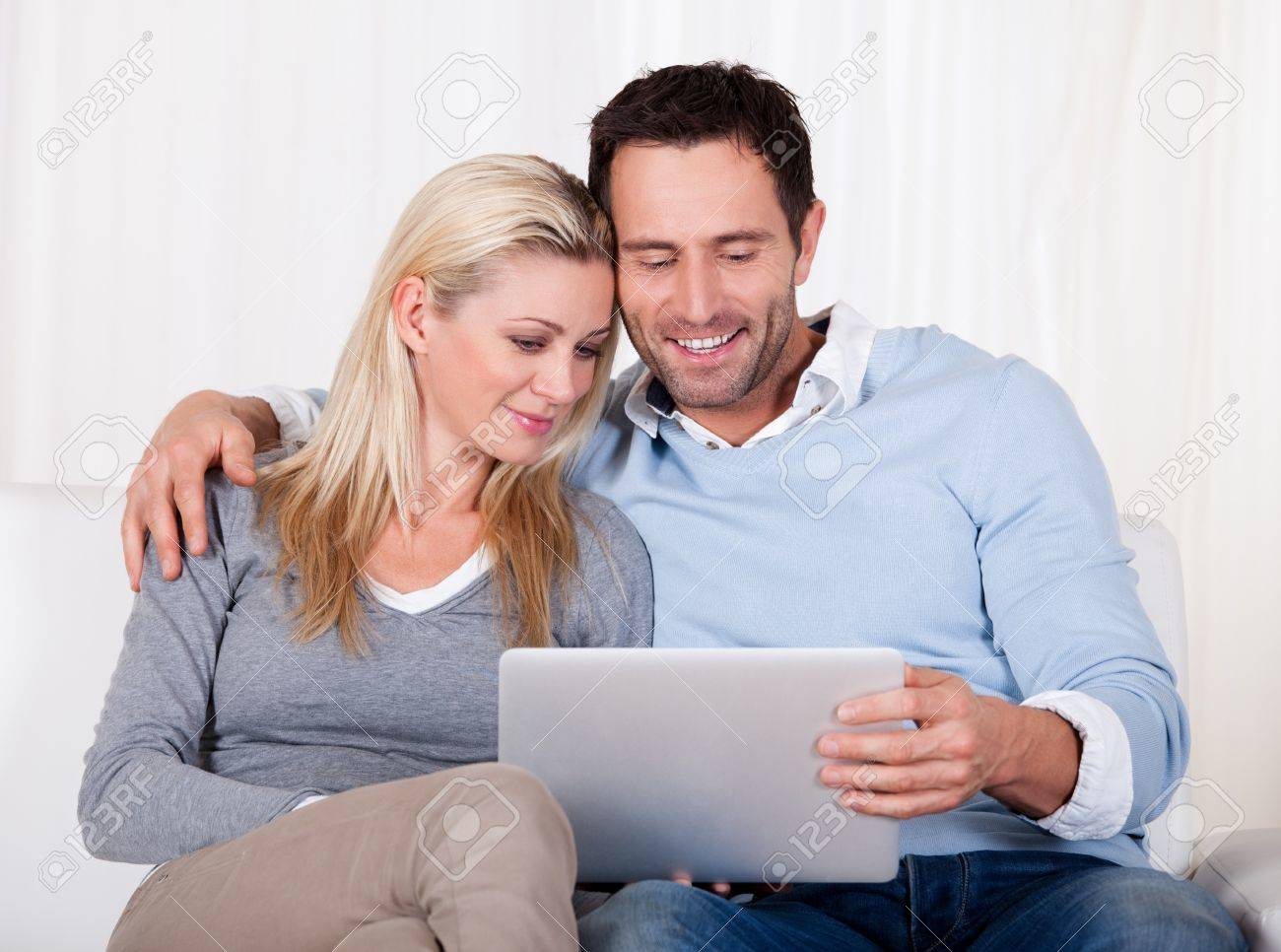 Beautiful young couple with lovely smiles sitting side by side on a sofa looking at a tablet together Stock Photo - 16886341