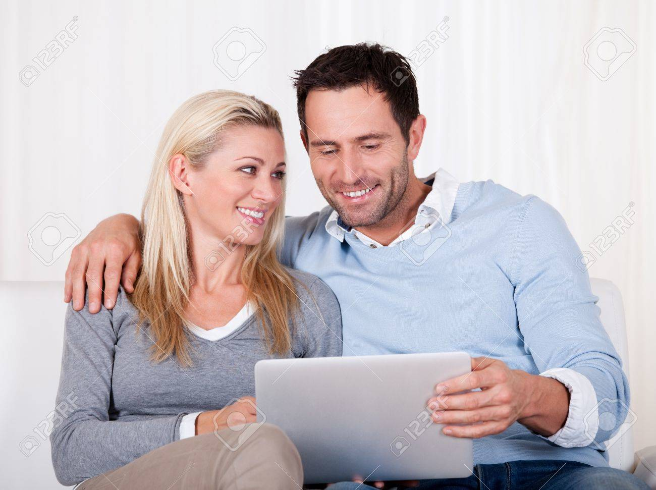 Beautiful young couple with lovely smiles sitting side by side on a sofa looking at a tablet together Stock Photo - 16886337