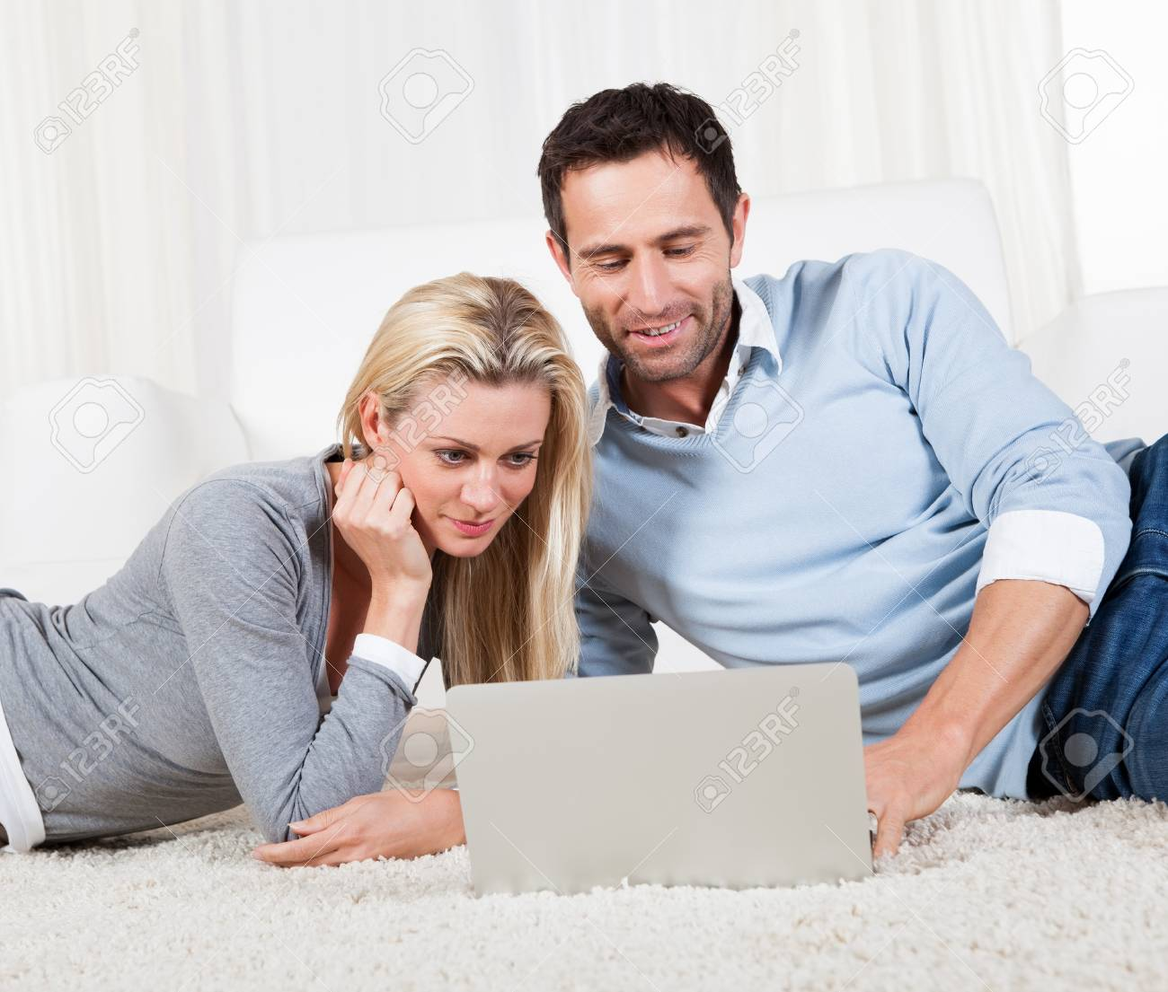 Attractive casual couple lying on their stomachs on a carpet with a laptop reading the information on the screen together Stock Photo - 16874277