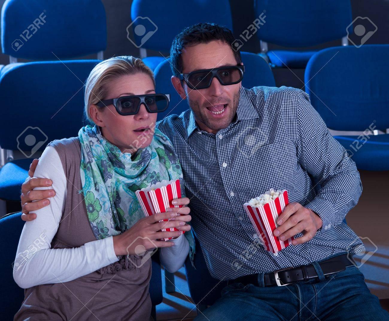 nuovo arrivo bambino scarpe da ginnastica a buon mercato Coppia, seduta in posti in un cinema con gli occhiali 3D che reagiscono  alla realtà dell'immagine dimensionale in una scena del film