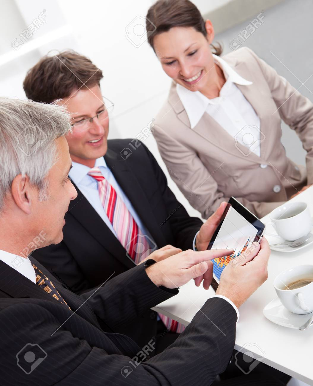 Business colleagues enjoying a coffee break smiling at something on the screen of a tablet held by one of the men Stock Photo - 17260917