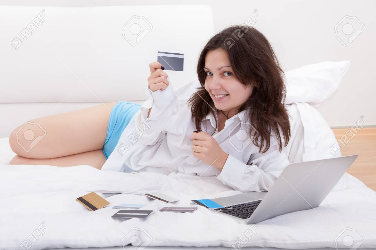 Young woman lying on her bed with a book and open laptop contemplating her numerous credit cards spread out in front of her Stock Photo - 17260809
