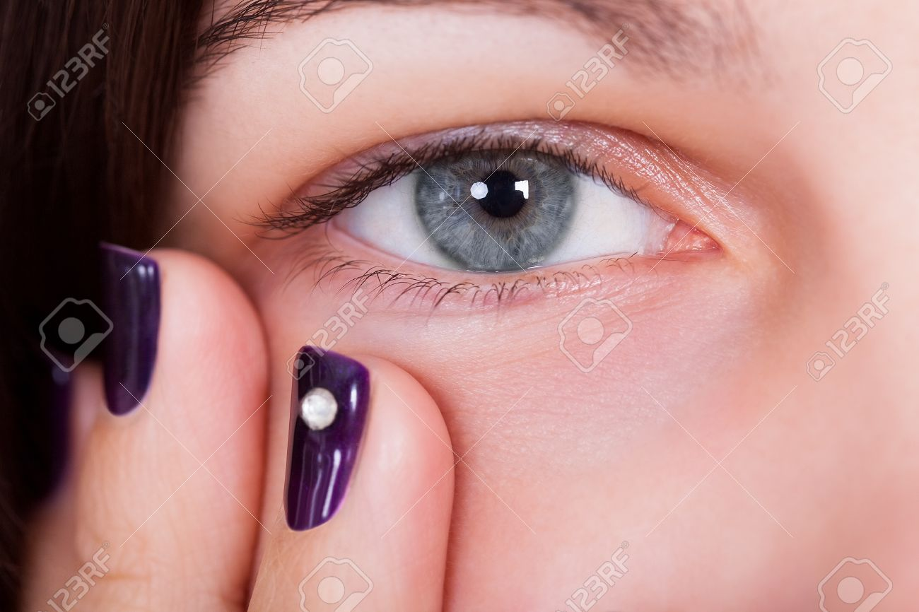 Closeup of a natural beautiful blue-grey female eye with fingertips showing manicured purple nails below Stock Photo - 17260816