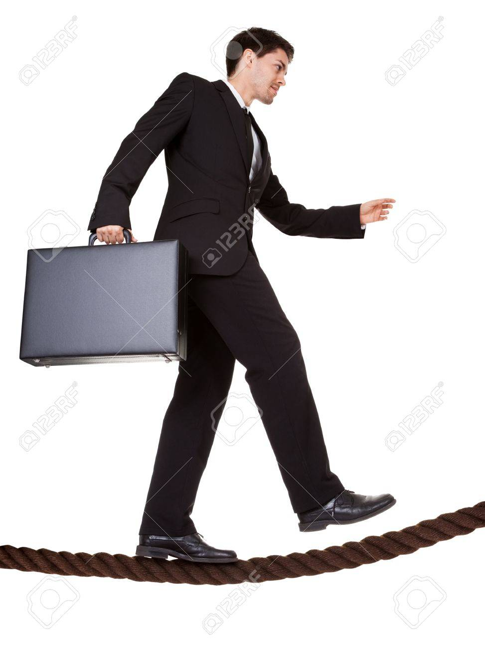 Conceptual image of a businessman carrying a briefcase balancing precariously as he walks a tightrope isolated on white Stock Photo - 17384634
