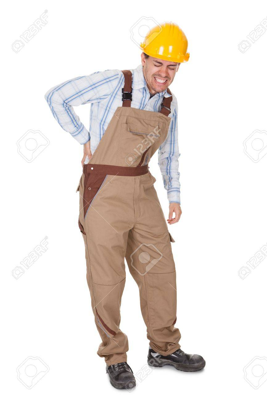 Workman with a back injury grimacing and clutching his lower back with his hand isolated on white Stock Photo - 17384612