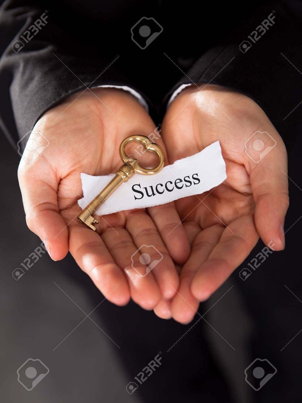 Businessman holding up a golden key in his hand Stock Photo - 17389802