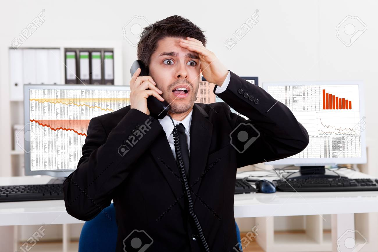 Worried stock broker talking on the phone backed by graphs depicting a crisis and a bear market with huge losses in the market Stock Photo - 17384550