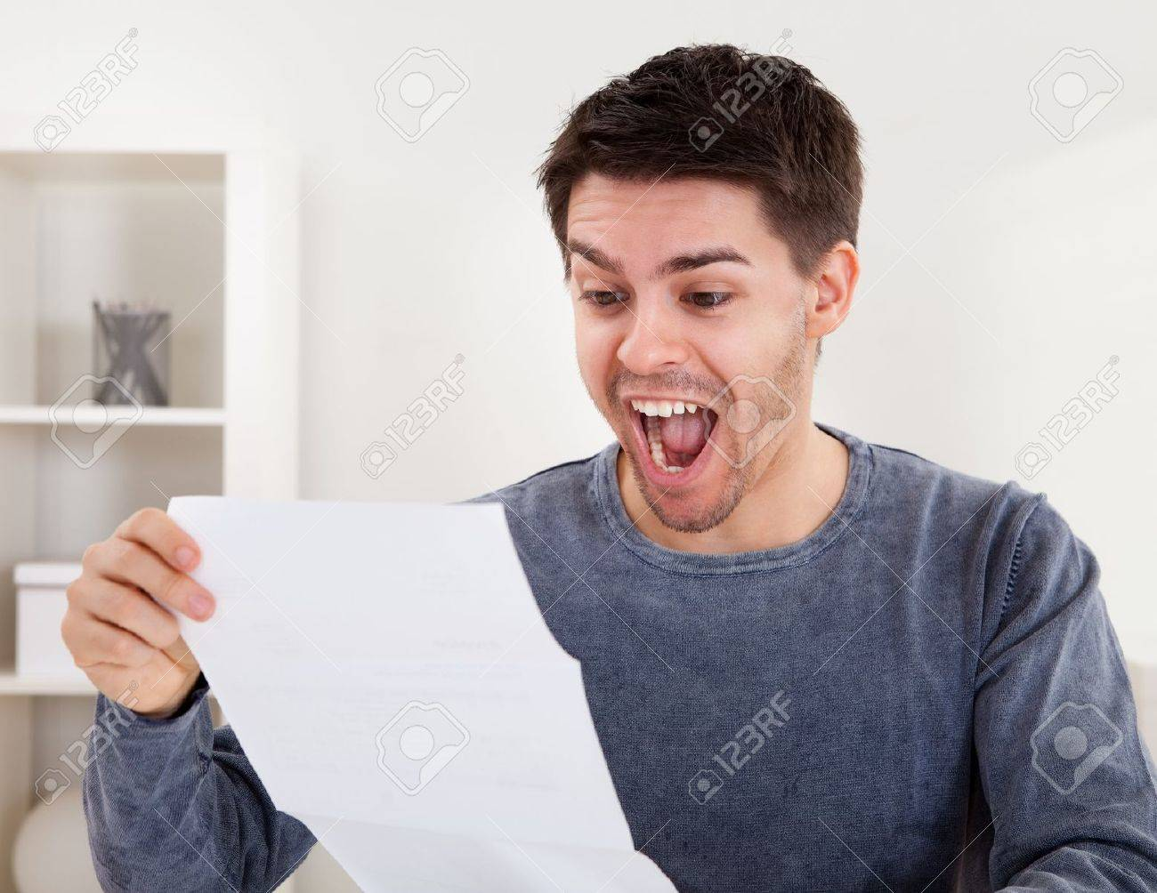 Exultant young man cheering at good news he has just received in a document that he is reading Standard-Bild - 17384508