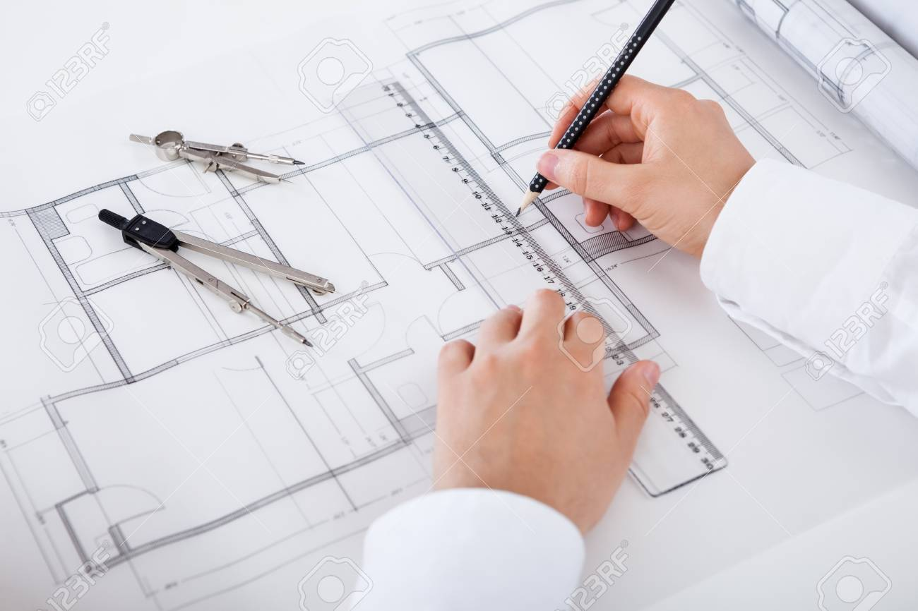 Closeup cropped image of a young male architect working on blueprints spread out on a table Stock Photo - 17384513