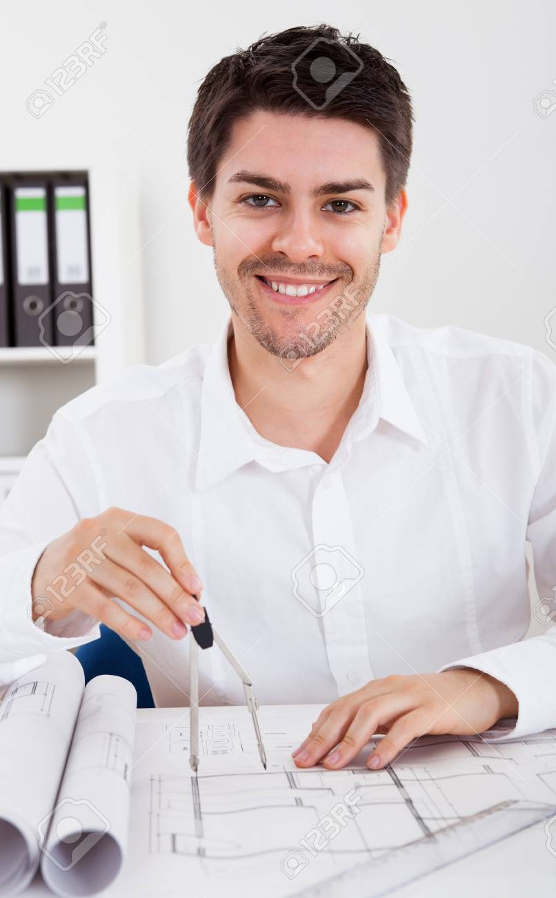 Closeup cropped image of a young male architect working on blueprints spread out on a table Stock Photo - 17384600