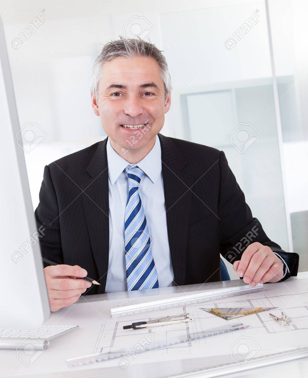 Portrait Of Mature Architect Male With Blueprint In The Office Stock Photo - 20535362
