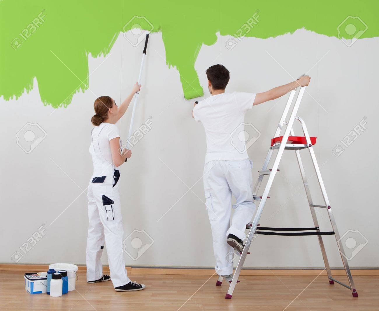 Person painting wall - Painting Wall Portrait Of Young Couple Painting Wall Together Stock Photo