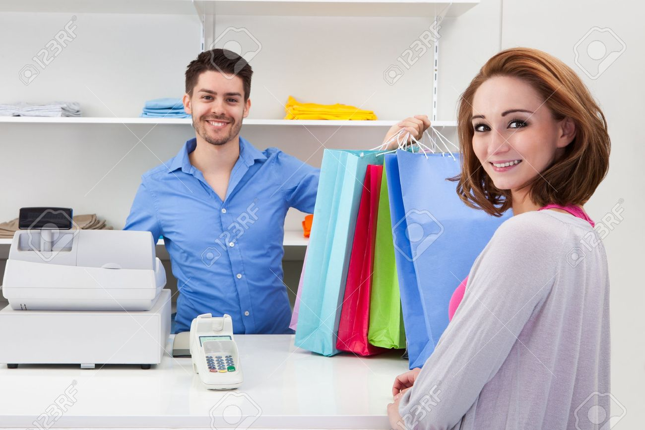 Happy Male Cashier Handing Over Shopping Bag To Customer Stock Photo - 20615370
