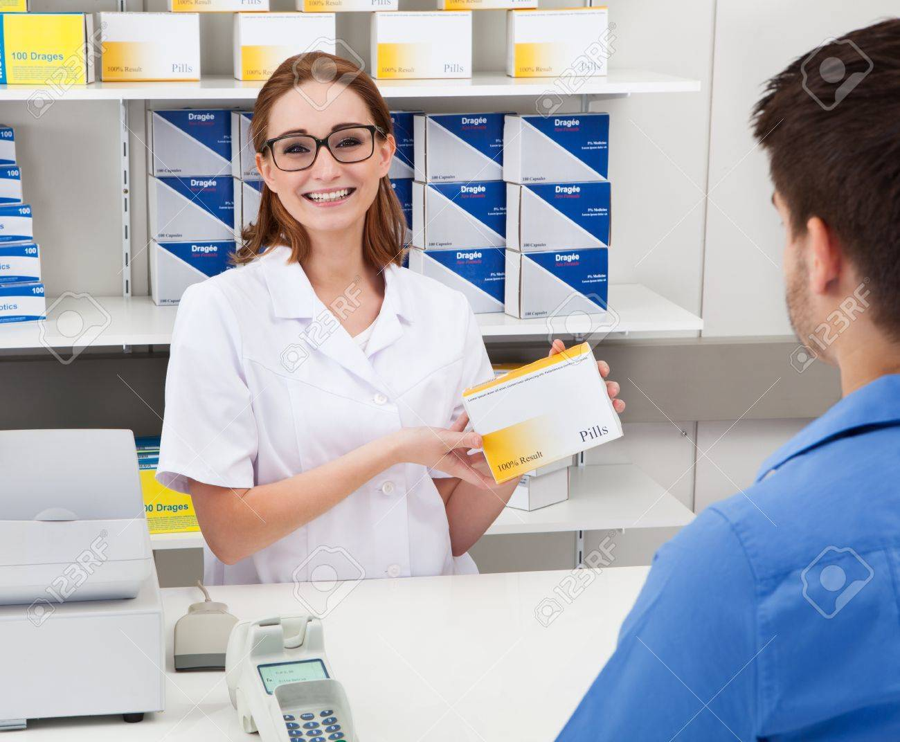 Happy Female Pharmacist Showing Drug In Pharmacy To Client Stock Photo - 20615443