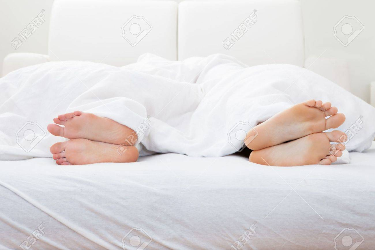 Close-up of couple's feet sleeping on bed in bedroom Stock Photo - 20790930