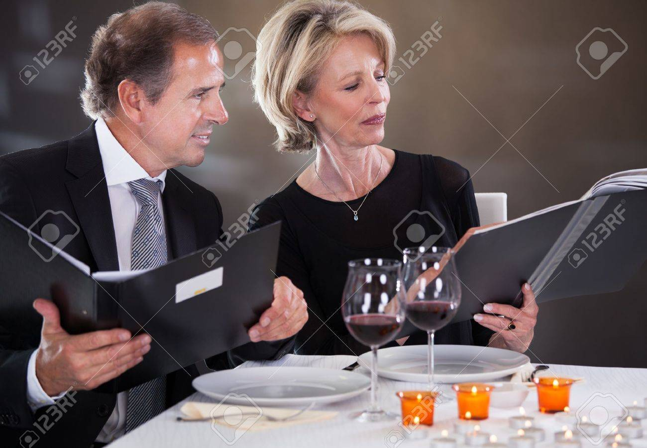 Mature Couple Sitting In Restaurant Woman Choosing Menu Stock Photo - 21234622