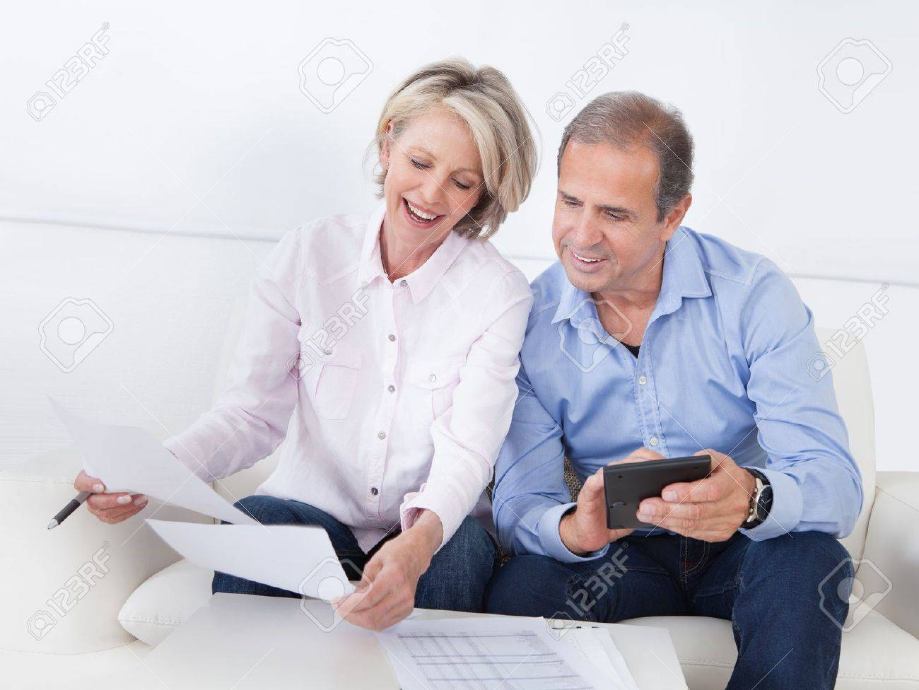 Portrait Of A Couple Sitting On Couch Enjoying Success Stock Photo - 21234769