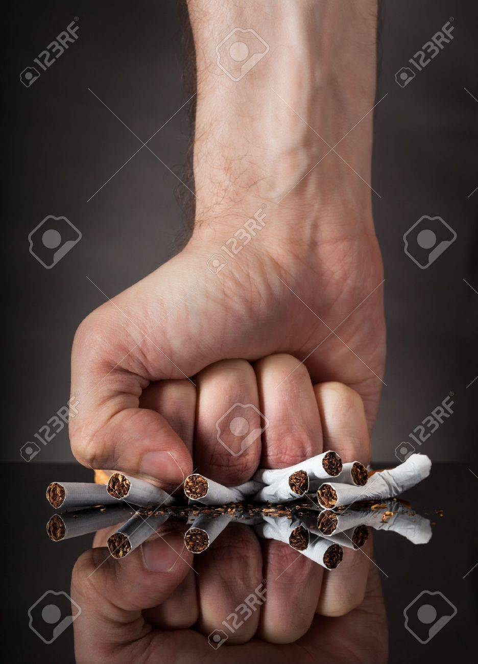 Close-up Of  Man's Fist Crushing Cigarettes Over Black Background Stock Photo - 21253832