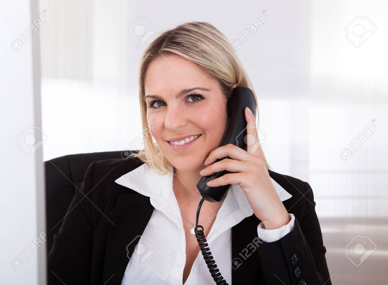 Happy businesswoman talking on telephone in the office Stock Photo - 21235192