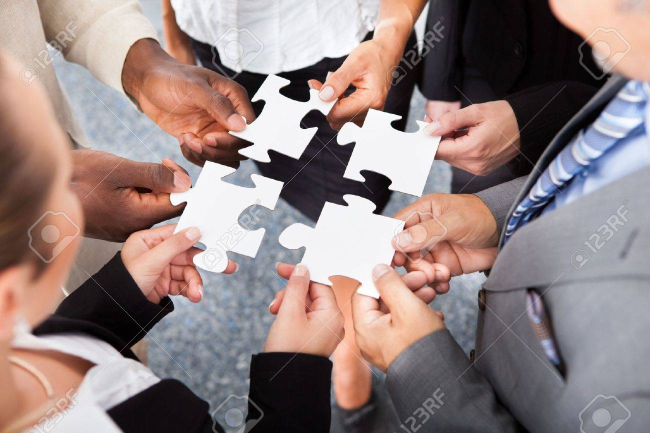 Close-up Photo Of Businesspeople Holding Jigsaw Puzzle Stock Photo - 21328394