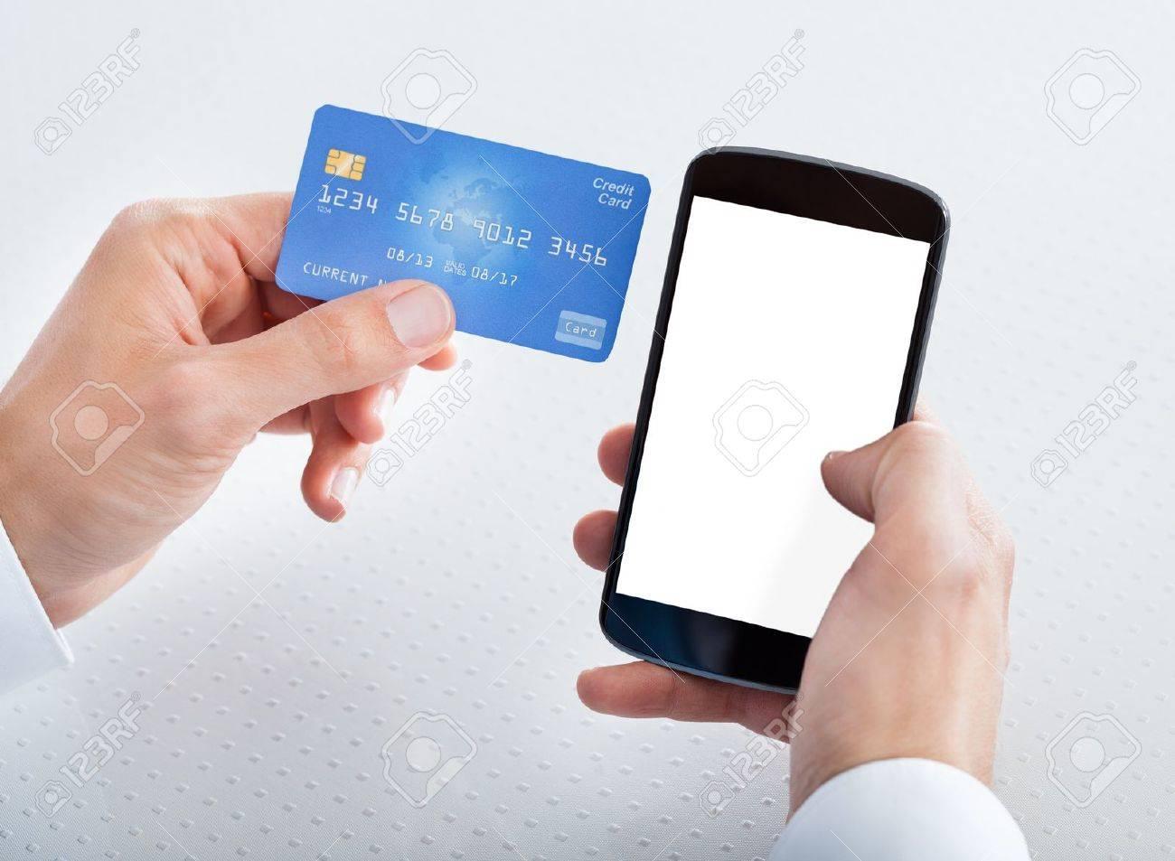 Man Hält Kreditkarte Und Handy-Checking Account Balance