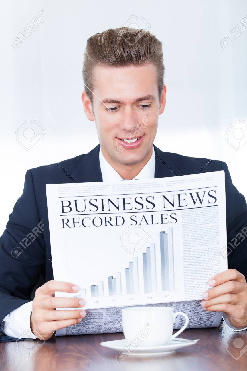 Happy Young Businessman Reading News On Newspaper Stock Photo - 21477832