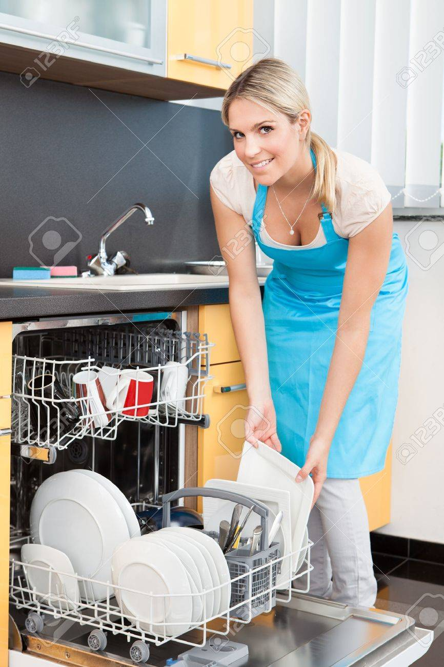 Happy Woman Putting Utensils In Dishwasher For Cleaning Stock Photo - 21478032