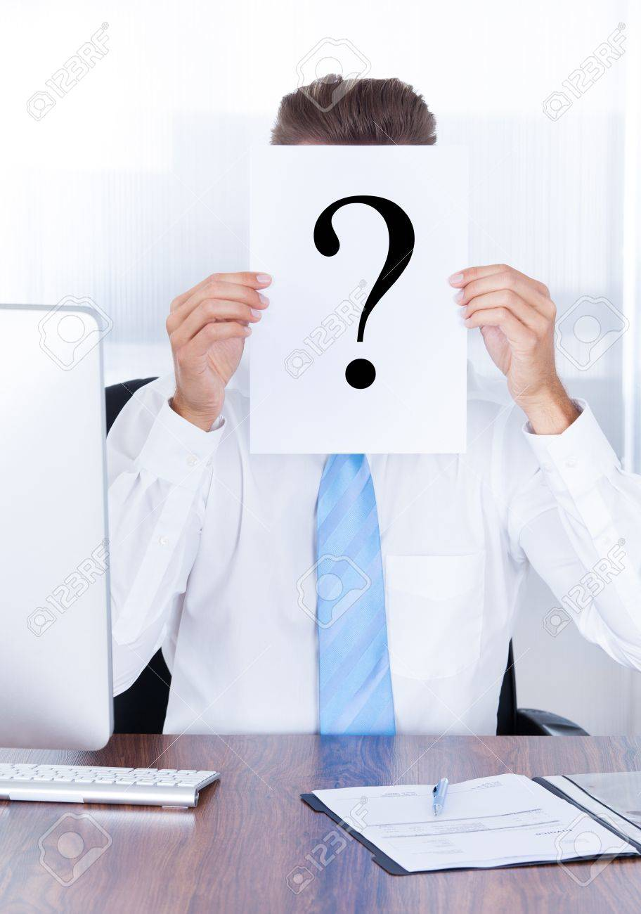Businessman Holding Question Mark Sign On Paper In Front Of Face Stock Photo - 21668719