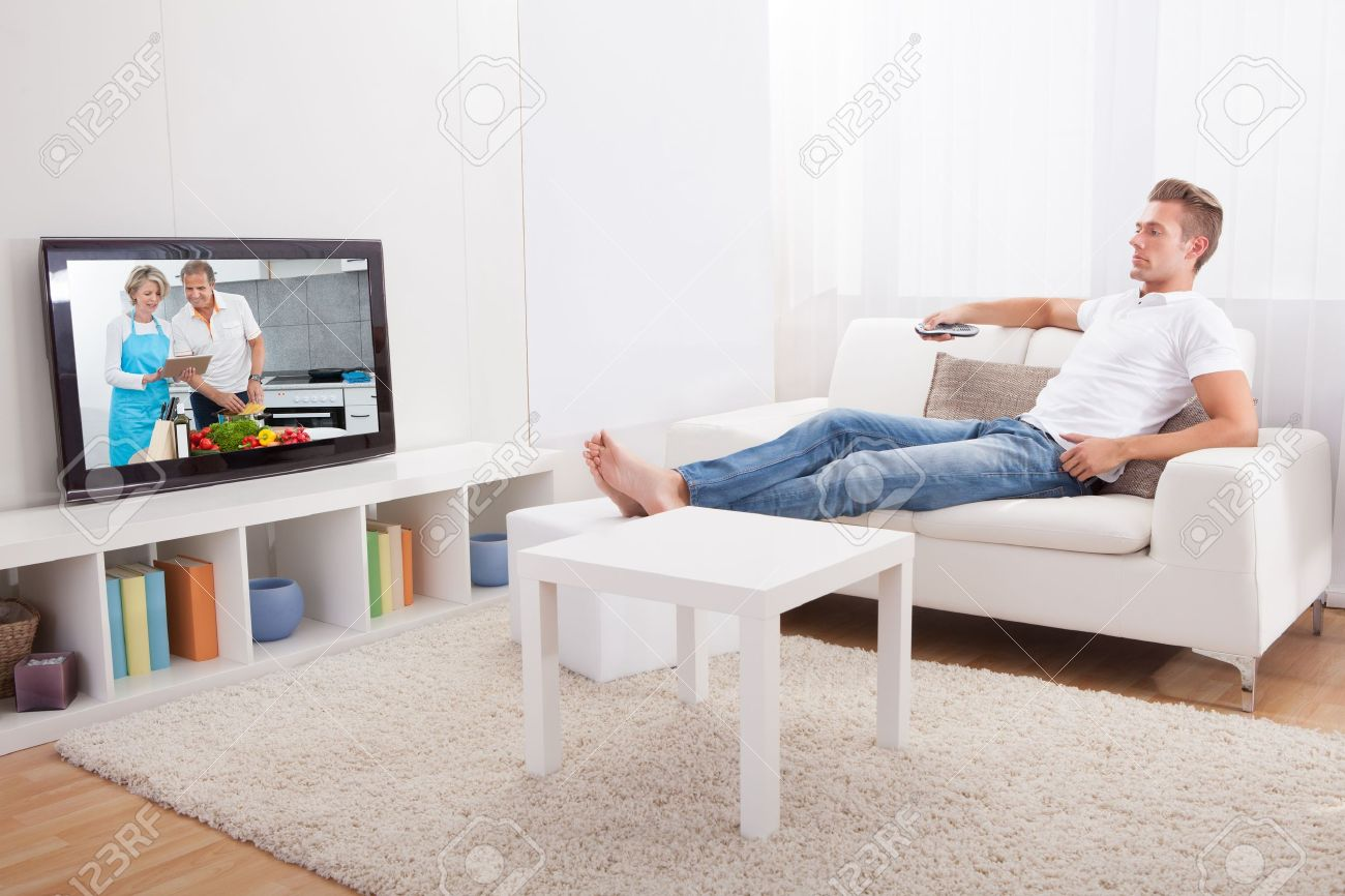 Young Man Sitting On Couch And Watching Movie At Home - 21668767