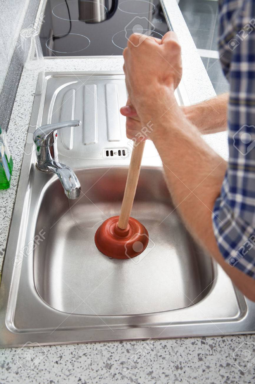 Closeup Of Man Using Plunger In Kitchen Sink Stock Photo   23490896