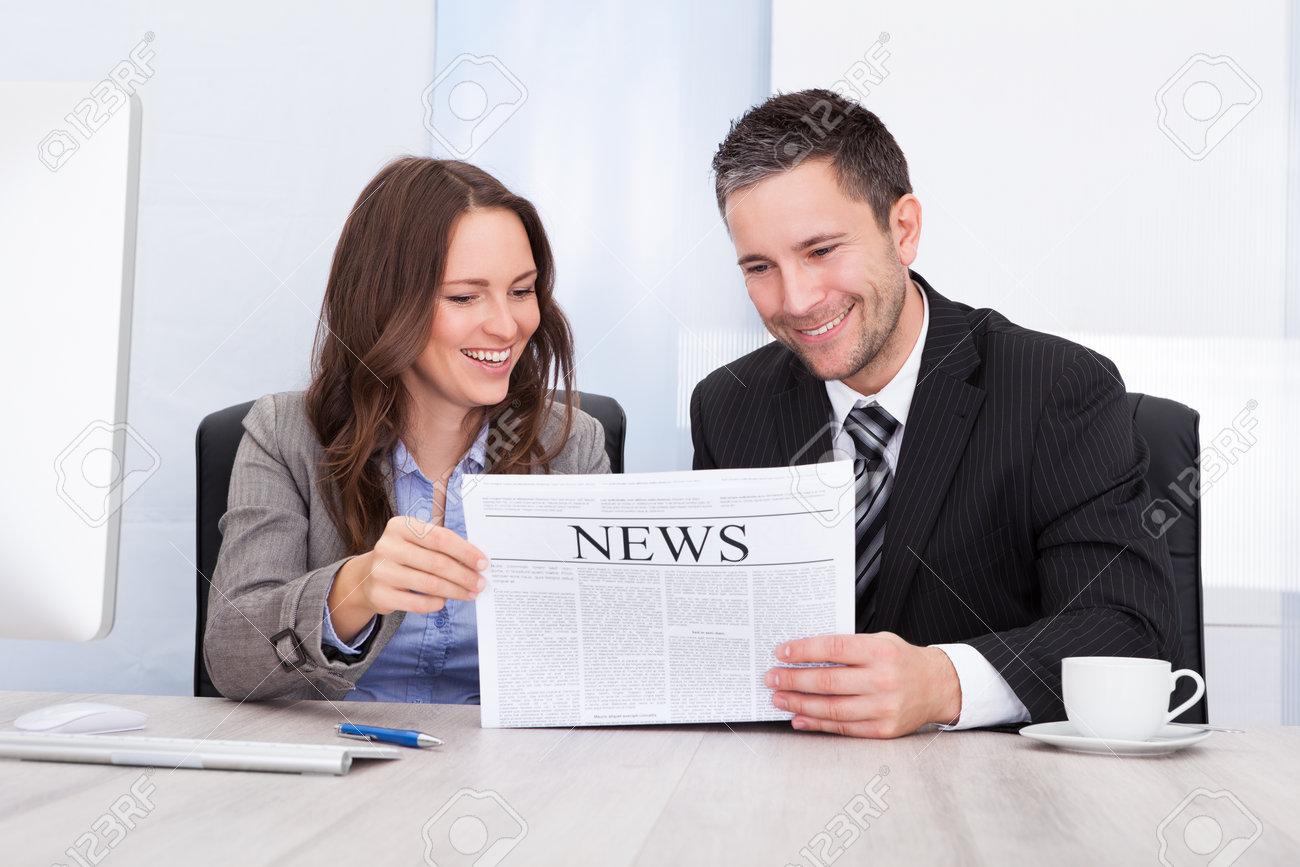 Portrait de gens heureuses de journal de lecture au bureau banque