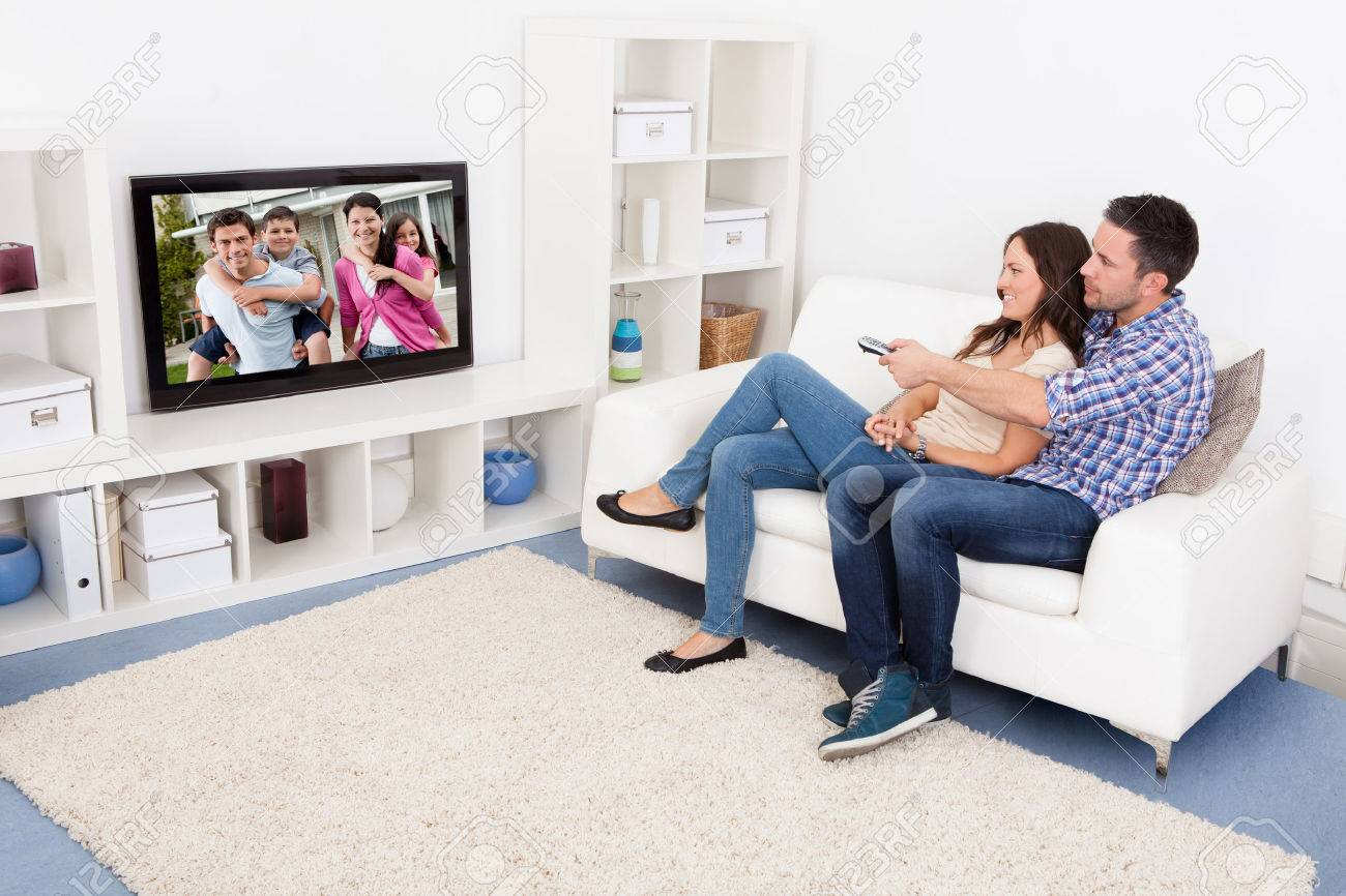 Happy Young Couple In Livingroom Sitting On Couch Watching Television - 24123100