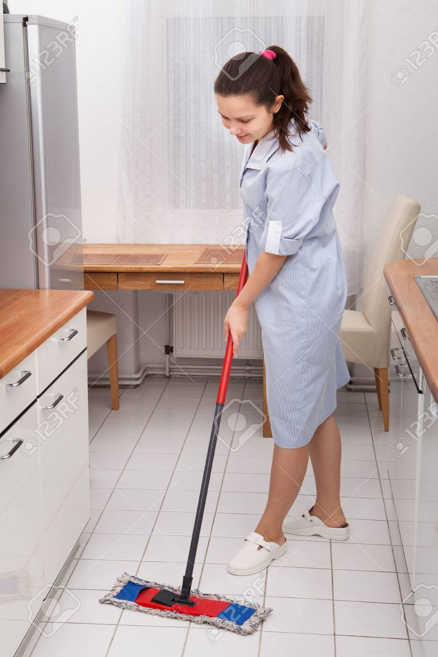 Portrait Of Young Maid In Uniform Cleaning Kitchen Floor Stock Photo    24285760