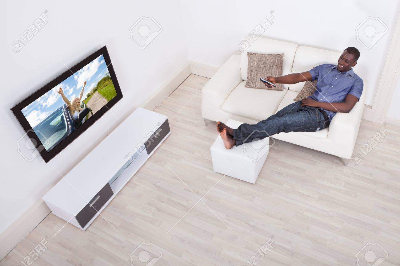 African Man Sitting On Sofa With Remote Holding In Hand Stock Photo ...