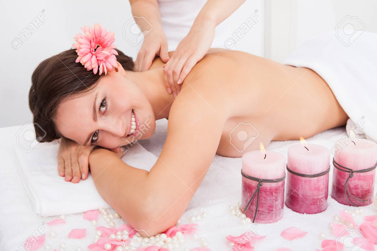 Smiling Young Woman Getting Massage Treatment From Masseuse Stock Photo - 25150093