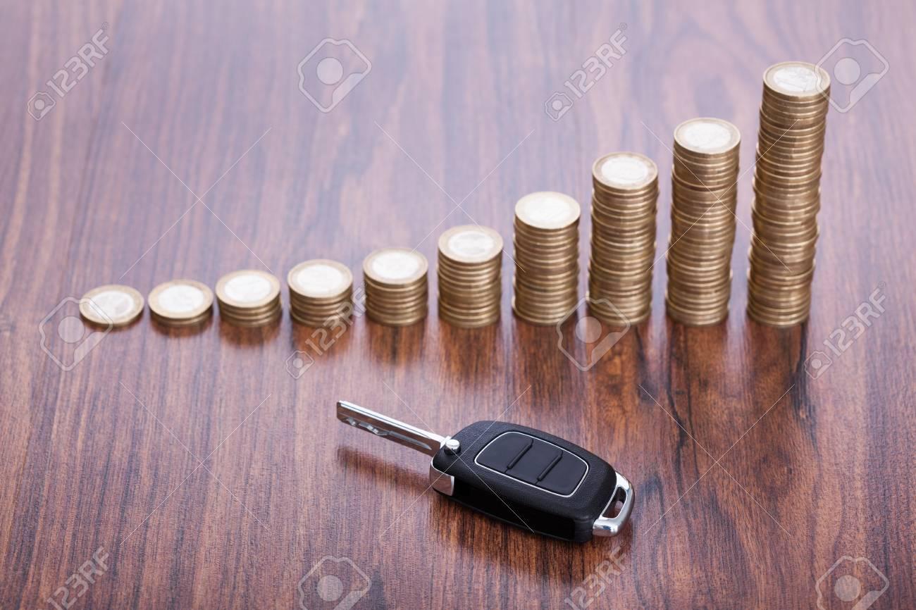 Pile de pièces de monnaie avec le noir de clef de voiture placée