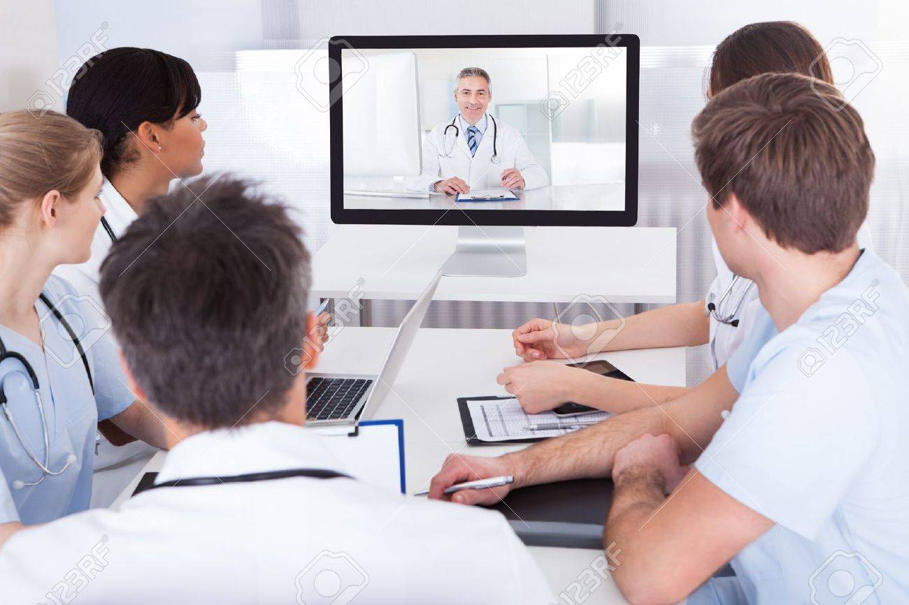 Group Of Doctors Looking At Online Presentation On Computer In Hospital - 25514818