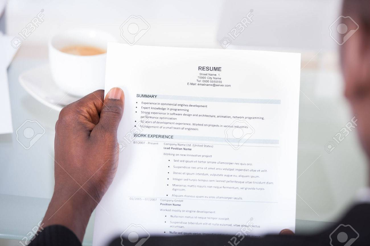 close up of a businessman looking at resume holding in hand stock
