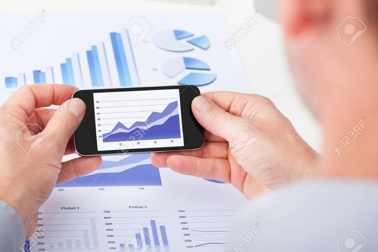 25537153-primer-plano-de-la-mano-de-la-persona-usando-el-tel%C3%A9fono-celular-encima-de-documento.jpg