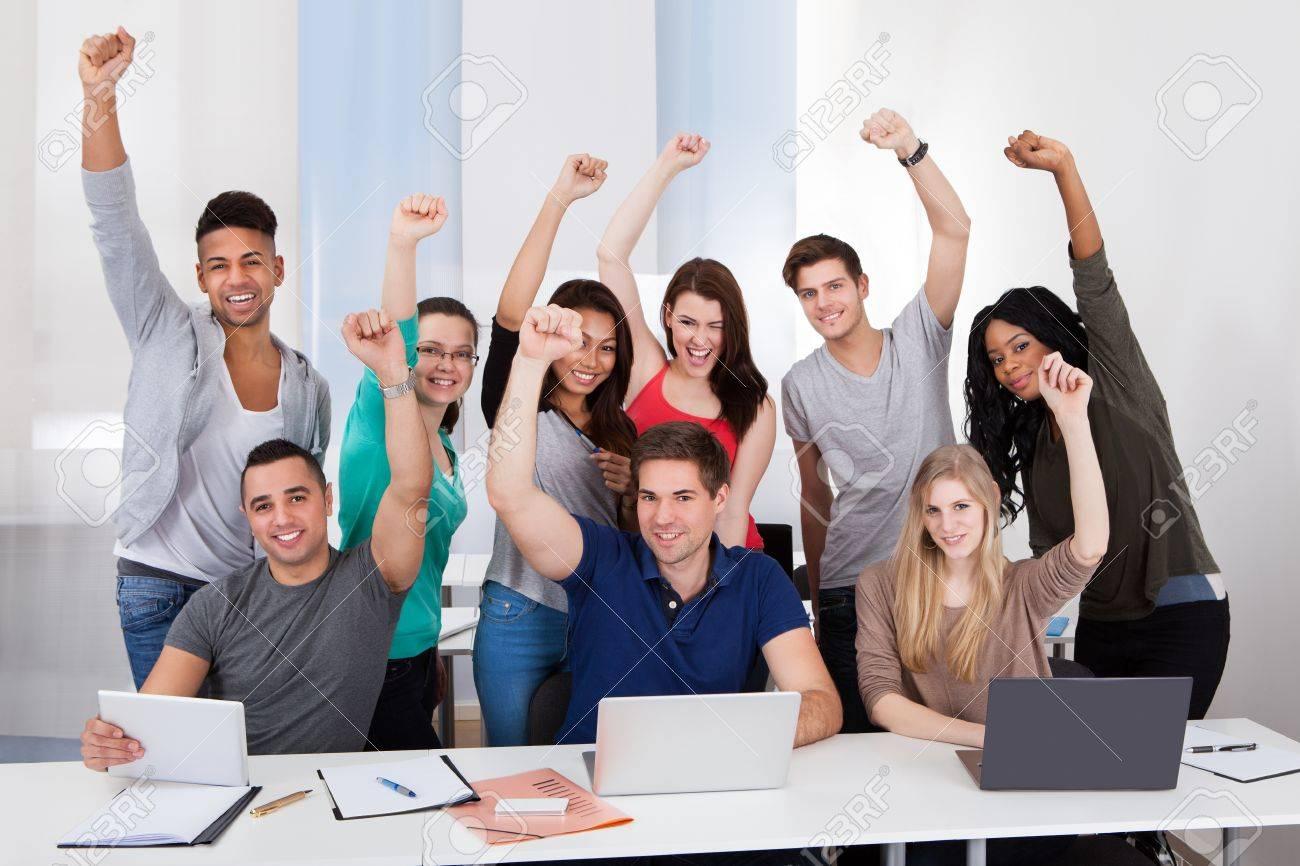 group portrait of happy multiethnic college students celebrating