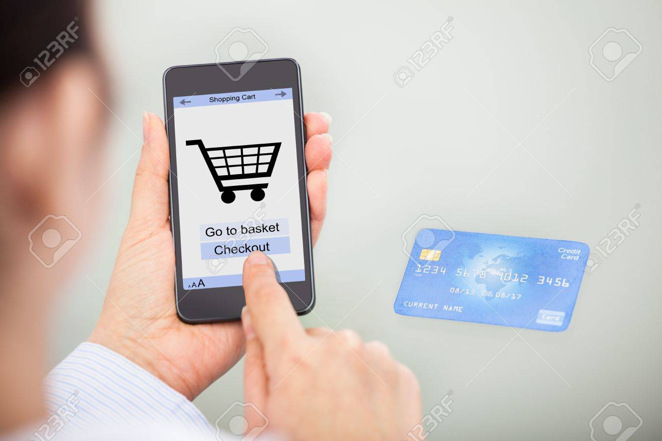 d85321f4474 Close-up Of Businessperson Shopping Online With Mobile Phone And Credit Card  Stock Photo -