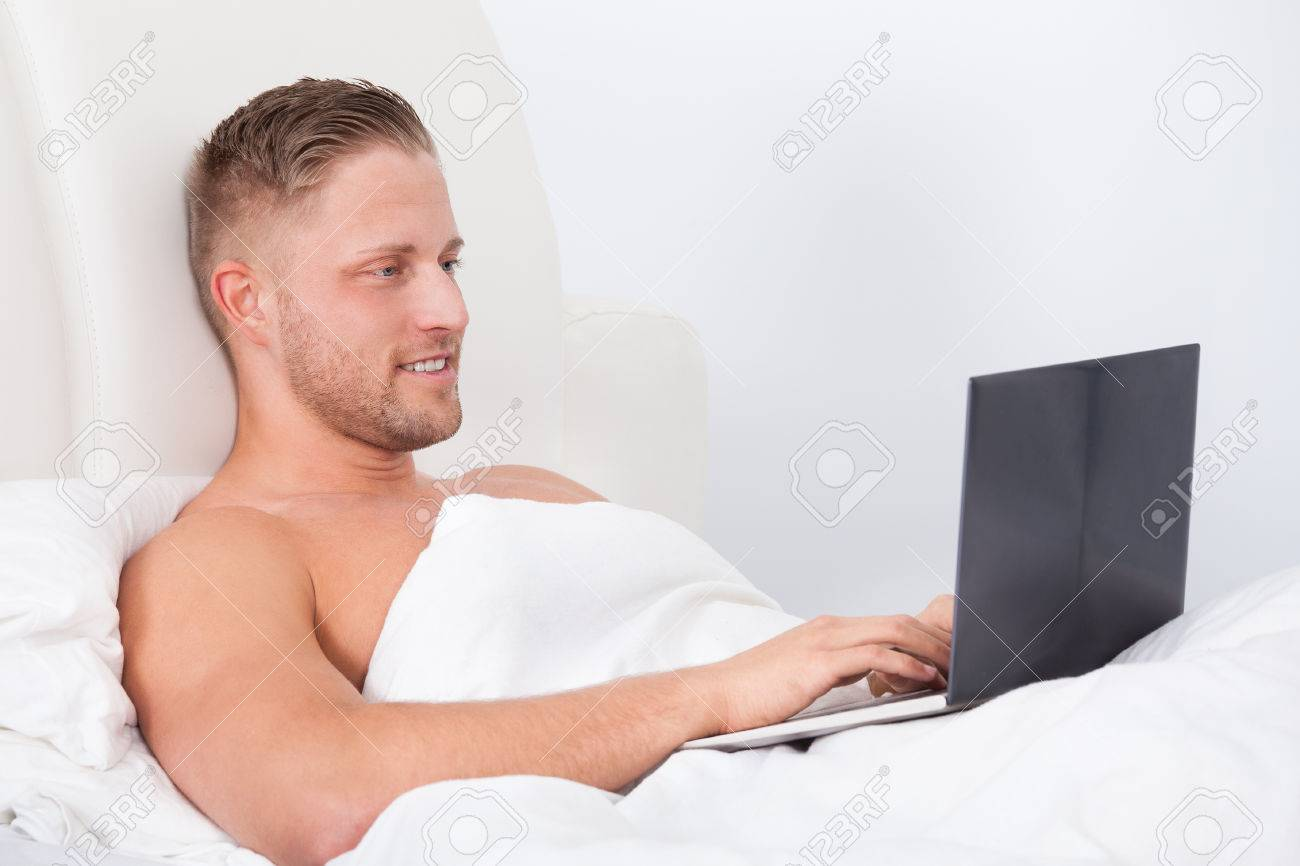 Man Sitting Up In Bed Against The Pillows Working On A Laptopputer  Smiling As He