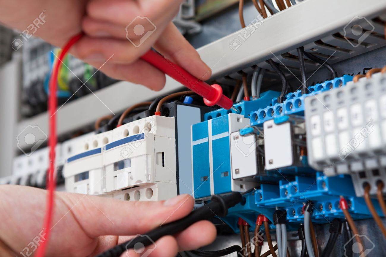 Electrical Stock Photos Royalty Free Images Wiring And Circuit Breakers Electrician Closeup Of Male Examining Fusebox With Multimeter Probe