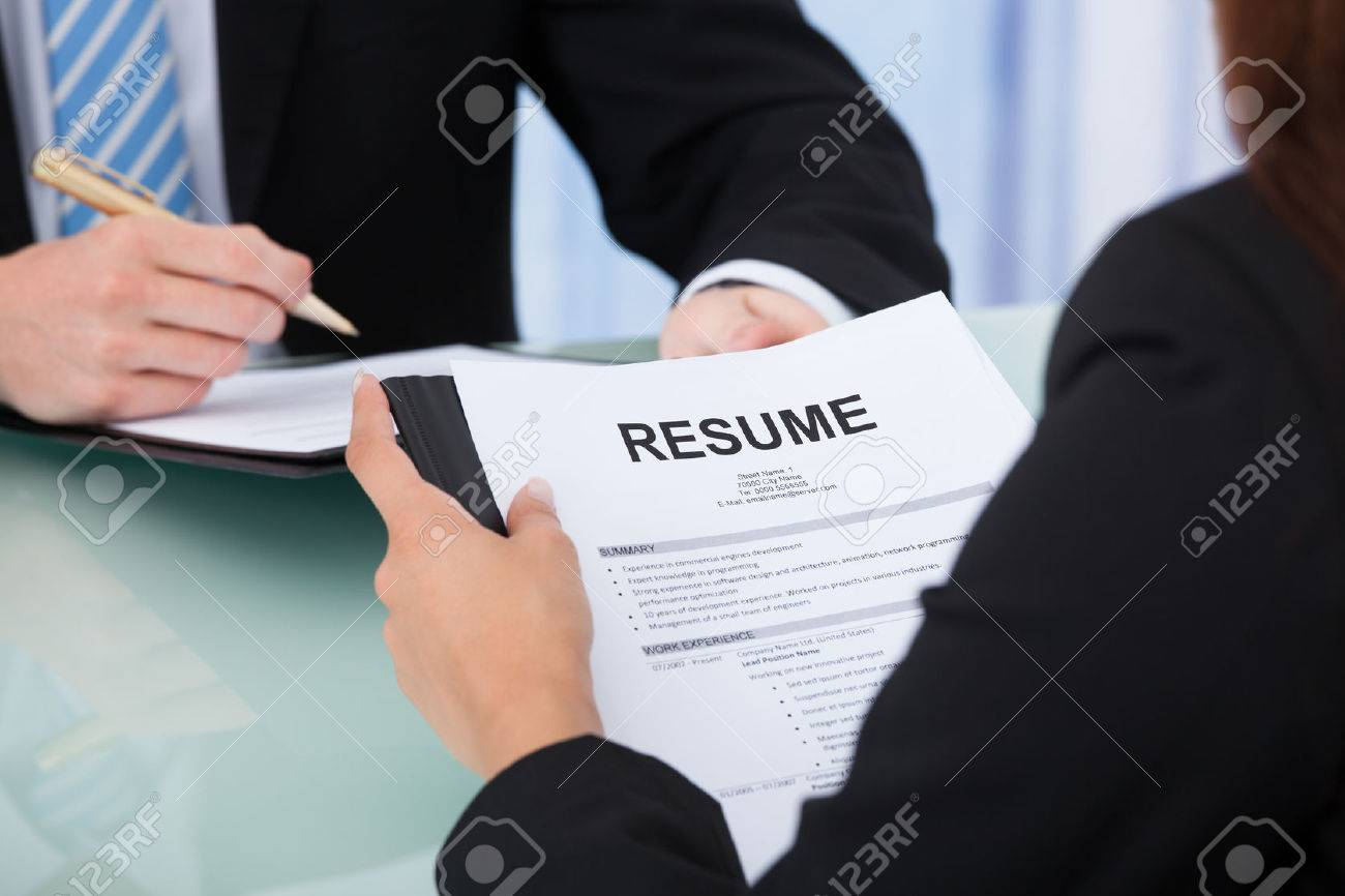 Cropped Image Of Female Candidate Holding Resume At Desk During